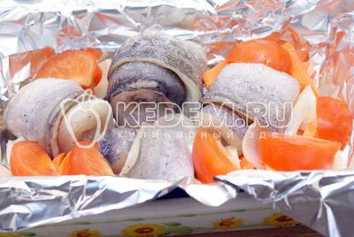 Фольгу отмерить в раза больше чем форма и выстелить дно. Смазать растительным маслом. Выложить рыбу, лук и морковь. Добавить ломтики помидор. Посолить сверху овощи. Кусочками нарезать сливочное масло и уложить сверху