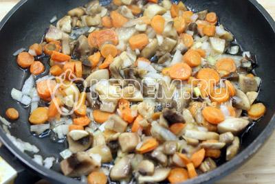 На 2 ст. ложках растительного масла обжарить половину мелко нашинкованного лука, кружочками нарезанную морковь и ломтиками нарезанные грибы. Обжаривать 2-3 минуты.