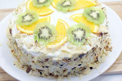 Обсыпать торт по бокам, сверху украсить ломтиками фруктов по желанию