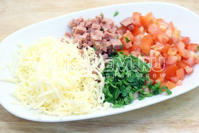 Для начинки смешать тертый сыр, нашинкованную зелень петрушки, кубиками нарезанные помидоры и сервелат