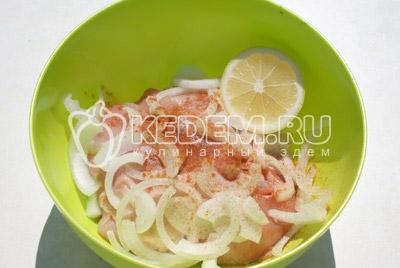 Выложить в миску куриные кусочки, полукольцами нарезанный лук. Добавить молотый перец и соль. Заправить соком лимона и растительным маслом
