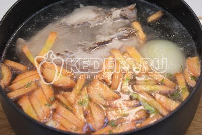 В кастрюлю добавить картофель и морковь, лук убрать. Варить 3-5 минут.