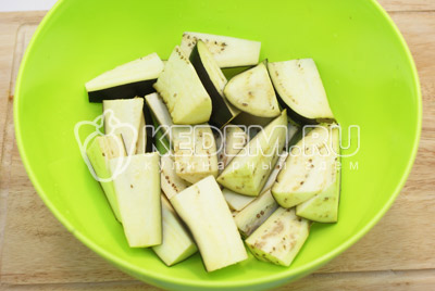Баклажаны вымыть и нарезать дольками. Выложить в миску и посолить, оставить на 20-30 минут.