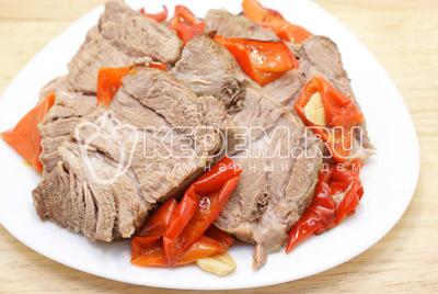 Готовое мясо немного остудить и нарезать порционными кусочками.#06Выложить на блюдо с ломтиками перцев и украсить веточками петрушки.