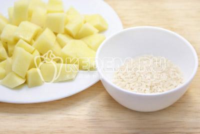 Картофель нарезать кубиками, рис промыть