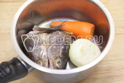 В кастрюлю сложить очищенные морковь, лук, головы и хвосты рыбы