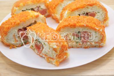 Нарезать порционными кусочками и выложить на плоское блюдо с  зеленью