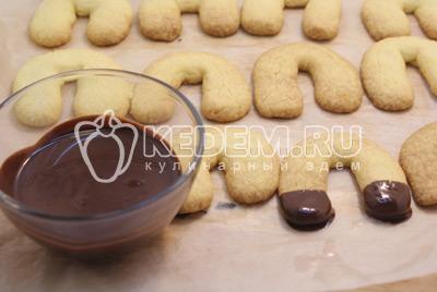 Остудить печенье и разогреть шоколад на водяной бане. Окунать печенье концами в шоколад и дать застыть на пергаменте