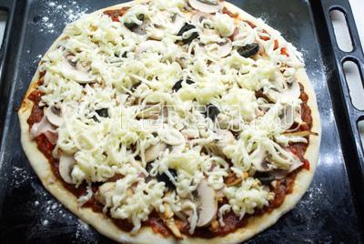 Моцареллу натереть на тёрке и посыпать пиццу.