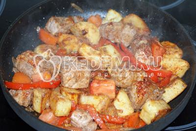 Добавить картофель и помидоры порезанные мелким кубиком. Всё перемешать и тушить 2-3 минуты