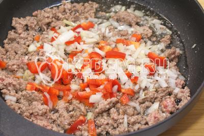 Перец и лук очистить и нарезать кубиками. Добавить в сковороду с фаршем овощи и обжаривать 2-3 минуты