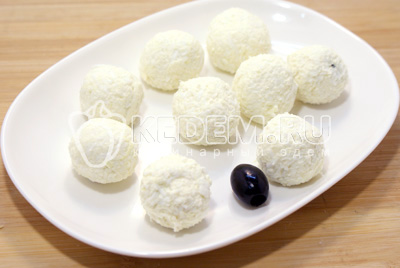 В чистые руки взять немного массы, уложить маслину и скатать шарик. Так же проделать с остальной массой