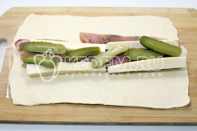 Тесто раскатать в длинный  пласт, выложить начинку из курицы, сыра и огурчиков
