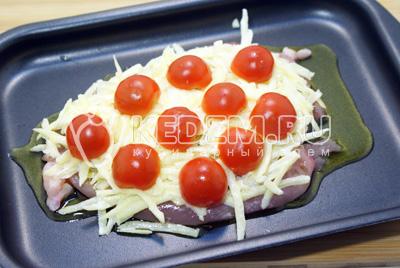 Выложить поверх отбивной картофель и половинки помидоров