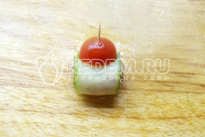 Оставшиеся помидоры черри разрезать пополам. Затем, в каждую пластинку  из огурца заворачиваем начинку,  закрепляем зубочисткой и нанизываем половинку помидорки.