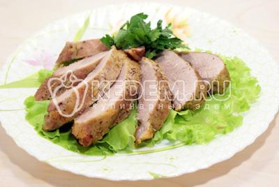 Готовое мясо немного остудить и нарезать ломтиками. Выложить на блюдо с листьями салата и зеленью
