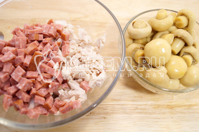 В миске смешать мелко нарезанное куриное филе, кубиками нарезанный сервелат. Добавить мелко нарезанные грибы