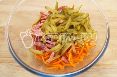 В миске смешать морковь по-корейски, соломкой нарезанный сервелат и огурчики
