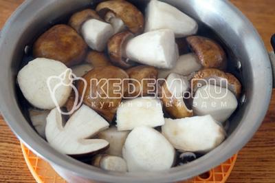 Большие грибы разрезать на половинки. Толстые ножки нарезать ломтиками в размер маленьких грибов. Вскипятить воду и варить грибы 5-7 минут