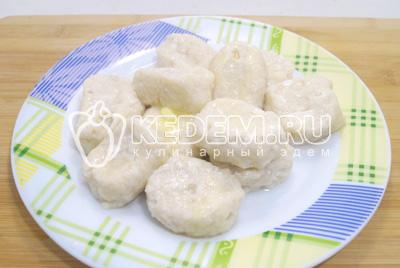 Выложить готовые вареники в миску и заправить хорошим количеством сливочном масла. Посыпать мелко нашинкованным зеленым луком.