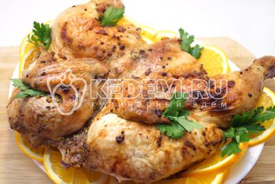 Готовую курочку немного остудить. Выложить на блюдо с ломтиками апельсинов и зеленью.