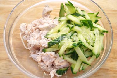 В миску нарезать курицу и соломкой нарезать огурец.