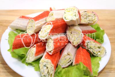 Разрезать палочки пополам наискосок. Выложить на блюдо с листьями салата.