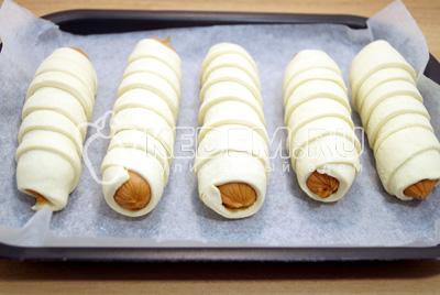 Завернуть каждую сосиску в полоску теста и выложить на противень с пергаментом, швом вниз.