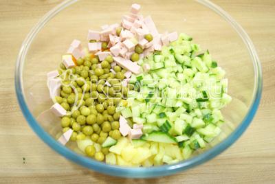 Добавить кубиками нарезанную колбасу, свежий огурец и горошек.