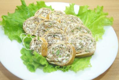 Нарезать порционными ломтиками и выложить на блюдо с листьями салата.