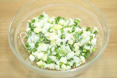 В миску мелко нарубить свежий зеленый лук и отварные яйца.  Немного посолить и перемешать.