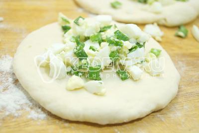 Разделить тесто на небольшие колобки и немного раскатать. Выложить начинку.