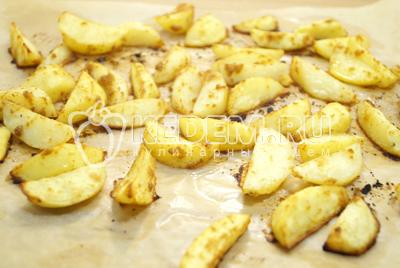 Готовые картофельные дольки немного остудить и снять с пергамента.