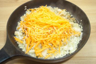 Добавить тертую морковь и обжаривать еще 2-3 минуты на среднем огне.