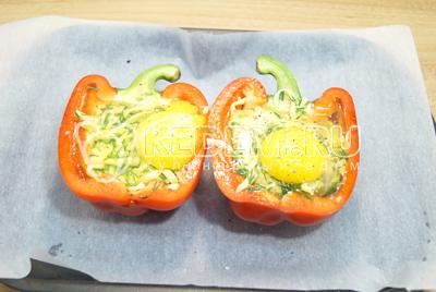 Разбить в каждую половинку по одному яйцу, немного посолить и поперчить сверху.