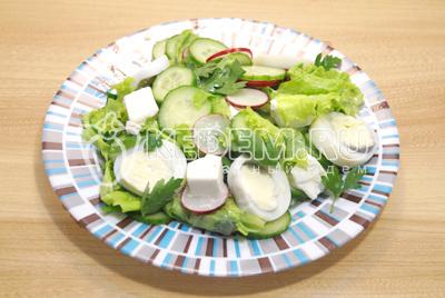 Выложить салат на сервировочное блюдо. Сверху выложить кубиками нарезанный сыр, кружочками нарезанное отварное яйцо и листья петрушки.