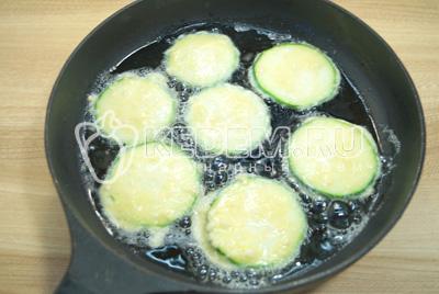 Окунать колечки кабачка в кляр и обжарить на сковороде с двух сторон до золотистой корочки на растительном масле.