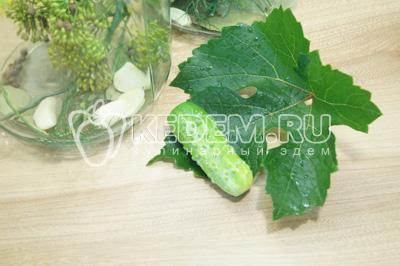 Каждый огурец завернуть в лист винограда и уложить плотно в банки.