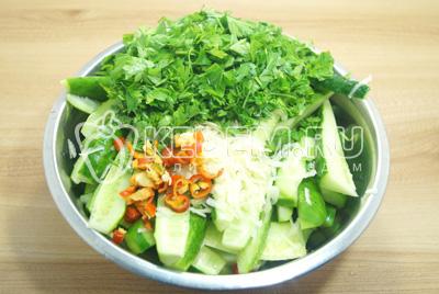 Добавить в миску с огурцами мелко нашинкованную зелень, измельченный перец и чеснок.