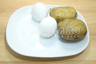 Отварить яйца и картофель, остудить и очистить.