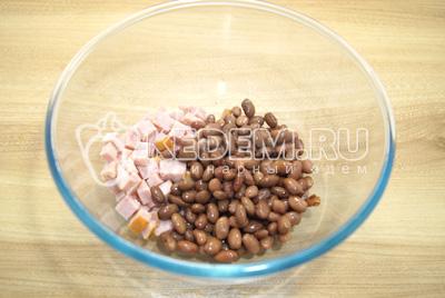 В миску кубиками нарезать ветчину и добавить фасоль без жидкости.