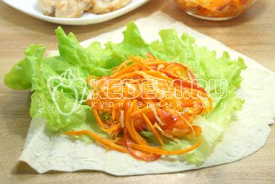 Выложить на лаваш листья салата, порцию овощного салата.