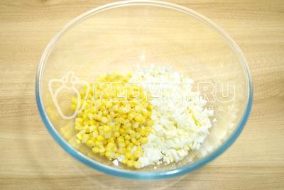 В миску мелкими кубиками нарезать яйца и добавить консервированную кукурузу.