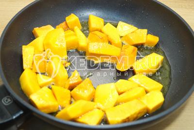 Обжарить кусочки тыквы на сковороде с растительным маслом.