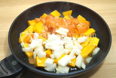 Добавить кубиками нарезанный лук и помидор. Обжаривать еще 2-3 минуты.