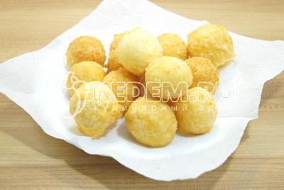 Готовые золотистые шарики выложить на блюдо с салфетками.