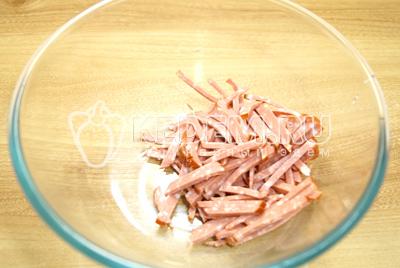 Нарезать колбасу соломкой в миску.