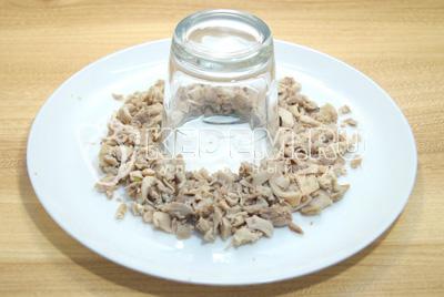 Мелко нарезать куриное мясо и выложить на блюдо вокруг стакана.