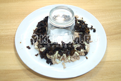 Нанести на слой мяса майонезную сетку. Выложить мелко нашинкованный чернослив.