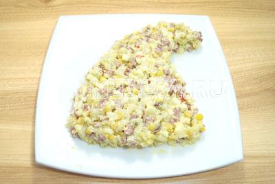 Выложить на плоское блюдо салат в виде колпака.
